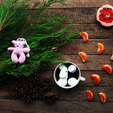 tea candles: Winter decoration. Composition on wood background. Hot tea, candles, cut grapefruit. Christmas. Christmas mood. Christmas spirit. Fir branches. Tangerine slices. Cones Stock Photo