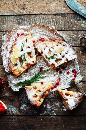 sprinkled: Pieces of apple pie sprinkled with powdered sugar. Homemade cut apple cake decorated slices of lemon and green spruce branches and pomegranate seeds on a wooden background. Rustic dark food style. Stock Photo
