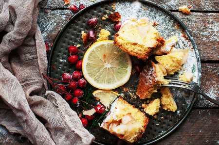 sprinkled: Pieces of apple pie sprinkled with powdered sugar. Homemade cut apple cake decorated slices of lemon and green spruce branches on a wooden background. Rustic dark food style.