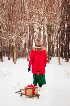 ski walking: Girl enjoying a day out playing in the winter forest. Girl walking up ski sled. The girl in a red jacket and skirt green pyanet sled with gift wrapped a red ribbon in the winter woods. Stock Photo