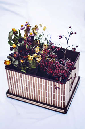 dried flower arrangement: Red and yellow dried roses in a box on a white background. Wood flower box. Red flowers in wooden box.  Red roses arrangement flower in a brown carton box.