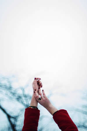 spreading arms: Woman spreading arms to sky. Arm stretching out. Reach for the sky. Girl open arms outdoor under blue sky. Women young hands with red nails, rings in a red coat, his hands reach for the sky.