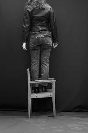 nude adult: Girlish legs in torn jeans on black background. Beautiful girl balances on back of  black background. Artwork.The girl in jeans standing on a chair backwards, his head cut off. Black-and-white photo.