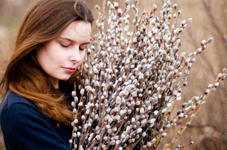 armful: Portrait of a beautiful young girl with a huge armful of willow in hands. Young woman gardening.