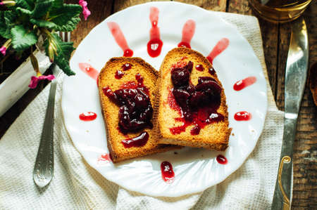 dulcet: Toast with jam and cup of tea on old wooden table. Delicious toast with jam on table close-up. Stock Photo