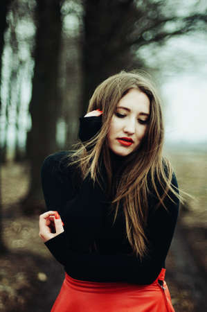straight jacket: Beautiful young girl with long straight hair, light make-up in a stylish trendy in a black jacket and red leather skirt in black hat outdoors in a park