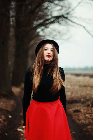 leather skirt: Beautiful young girl with long straight hair, light make-up in a stylish trendy in a black jacket and red leather skirt in black hat outdoors in a park
