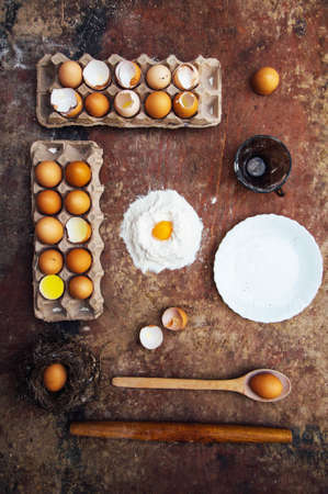 mess: Baking cake ingredients - bowl, flour, eggs, egg whites foam, eggbeate on wood chalkboard from above. Cooking course or kitchen mess poster concept. Flat lay. Rustic style Stock Photo
