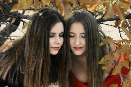 Retrato de hermosas niñas vestidas con ornoe y vestido largo rojo. Dos muchachas, amigos, poztruyut en el parque de la primavera en el fondo de árboles verdes. Dos amigos sonrientes jovenes, retrato, verano