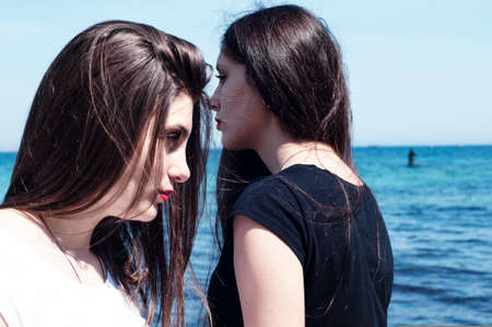 slavonic: Sisters at beach hugging each other. Portrait of beautiful young girls, sisters, against the backdrop of the sea. Young beautiful slavonic girls in white and black posing on the sea water