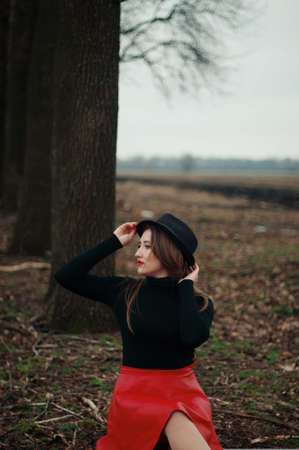straight jacket: Beautiful young girl with long straight hair, light make-up in a stylish trendy in a black jacket and red leather skirt in black hat outdoors in a park on a background of trees. The girl looks  camera Stock Photo