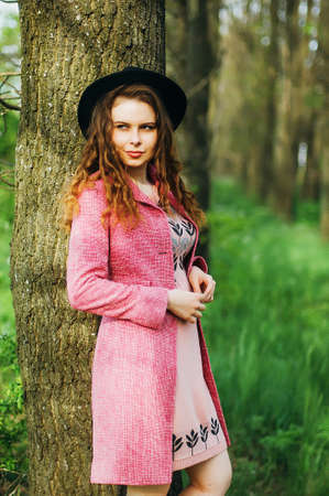 street shot: Portrait young elegant woman in pink coat and black hat. Fashion outdoors shot, street style concept. Photo toned  vsco filters. Spring portrait of stylish model, posing in the park