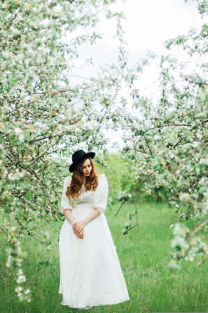 Young girl in a white dress and black hat in the in the white stock photo young girl in a white dress and black hat in the in the white flowers garden woman in a beautiful long dress posing on a meadow in the fruit mightylinksfo
