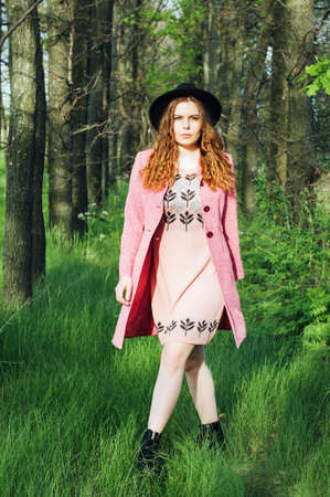 street shot: Portrait young elegant woman in pink coat and black hat. Fashion outdoors shot, street style concept. Photo toned  filters. Spring portrait of stylish model, posing in the park