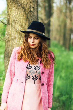 street shot: Portrait young elegant woman in pink coat and black hat. Fashion outdoors shot, street style concept. Blogger outfiit. Photo toned  vsco filters. Spring portrait of stylish model, posing in the park