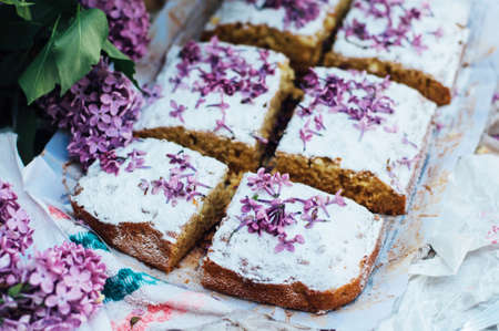 christmas baker's: Homemade delicious fresh vanilla cake with apples sprinkled with powdered sugar and decorated with flowers and branches of lilac on a white kitchen table. Dessert cake for a large family.  sweets Stock Photo