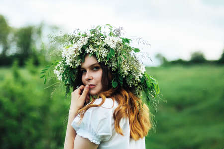 Young pagan Slavic girl conduct ceremony on Midsummer. Beauti girl dressed in a white blouse with embroidery, denim shorts, boots with grass Acacia wreath on his head against the background of nature