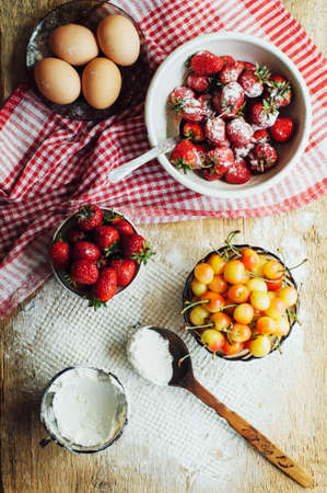 atmosphere: Cooking cake with fresh ingredients for preparing in cooking. Rustic dark atmosphere. Flour, eggs and fresh strawberries, cherries, butter, flour over on wooden background. Series, recipe step on step Stock Photo