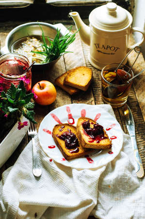 dulcet: Toast with jam and cup of tea on old wooden table. Delicious toast with jam on table close-up. Fresh cherry jam with toast for breakfast on rustic wooden background. Sweet cherry jam on toast. Stock Photo