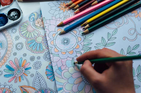 stress relief: Image of woman coloring, adult coloring book trend, for stress relief. top view. colorer - antistress with colored pencils. Adult coloring books. The woman draws thereby relieves stress Stock Photo