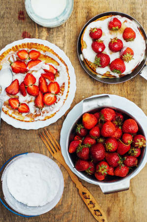 Strawberries and whipped cream  for dessert. Pancakes with  strawberries and sour cream. Stack of pancakes with fresh strawberry and balsamic glase in frying pan on wooden table. Rustic style Stock Photo