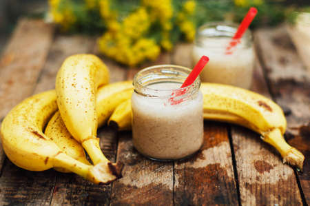 bl: Fruit Smoothies. banana smoothies with milk. Banana Smoothie on a wooden table. Healthy breakfast: banana smoothie with oatmeal. Banana smoothie in glass with fresh fruits on wooden background