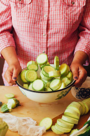 green stuff: The woman in the kitchen preparing a meal of fresh ripe green stuff long zucchini. Country style. Womens hands. Vegetable dish. Marinating squash before cooking