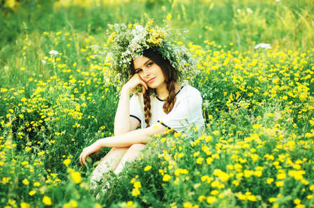 slavs: beautiful girl in wreath of flowers  in meadow on sunny day. Portrait of Young beautiful woman wearing a wreath of wild flowers. Young pagan Slavic girl conduct ceremony on Midsummer.