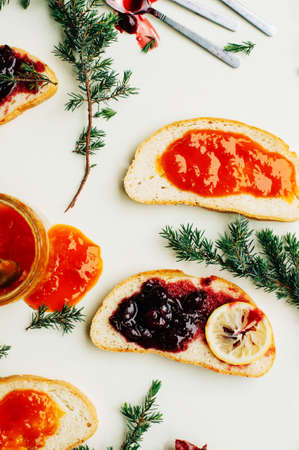 jelly sandwich: Homemade sandwiches with peach and cherry jam on a white background. It is decorated with fir branches. Butter and Jelly Sandwich. Flat lay. Stock Photo