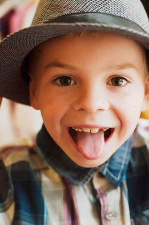 Childs happy face . Portrait of a Cute Kid.  little boy with short blond hair and brown yeas. Beautiful little boy seven years posing with a hat and denim shirt. Smailing boy