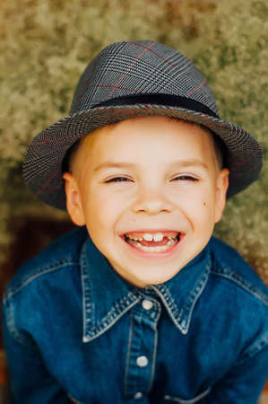 7 year old boys: Childs happy face . Portrait of a Cute Kid.  little boy with short blond hair and brown yeas. Beautiful little boy seven years posing with a hat and denim shirt. Smailing boy
