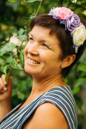 55 years old: A portrait of a middle age woman. Portrait of a beautiful woman 55 years old posing on the rim of the beautiful Silk flowers outdoors Stock Photo
