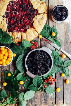 freshly baked berry pie. Blackberries pie with a slice missing. Berry pie preparation.   pie in summer with fresh picked blackberries.