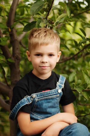Portrait of smiling seven year old boy. Seven year old boy  with brown eyes and blond hair. Young boy in a black T-shirt and denim overalls outdoor.  Boys portrait.