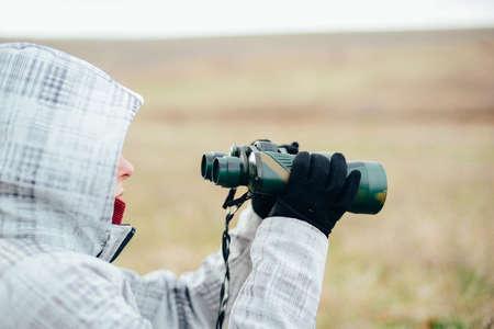 mujer mirando el horizonte: Young woman looking through binoculars on a autumn nature. Binocular, traveler, hiking.  young caucasian female hiker holding in his hand binoculars. Horizontal shape, front view,