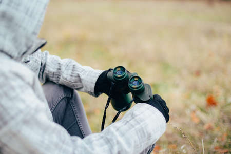 mujer mirando el horizonte: Young woman looking through binoculars on a autumn nature. Binocular, traveler, hiking.  young caucasian female hiker holding in his hand binoculars. Horizontal shape, front view,