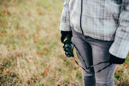 mujer mirando el horizonte: Mujer joven que mira a través de binoculares en una naturaleza del otoño. Binocular, viajero, el senderismo. joven excursionista mujer caucásica que sostiene en su mano binoculares. Forma horizontal, vista frontal,