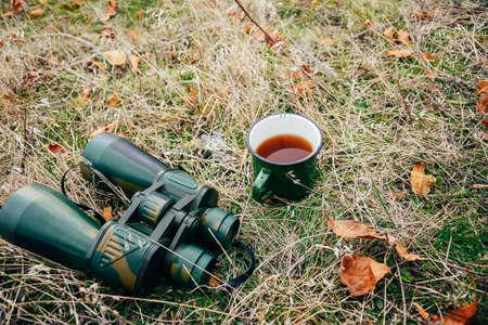 mujer mirando el horizonte: Mujer joven que bebe té en una naturaleza del otoño. Binocular, viajero, el senderismo. joven excursionista mujer caucásica que sostiene en su mano cuo de té. Forma horizontal, vista frontal,