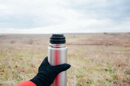 Young woman drinking tea on a autumn nature. Binocular, traveler, hiking.  young caucasian female hiker holding in his hand cuo of tea. Horizontal shape, front view, Stock Photo