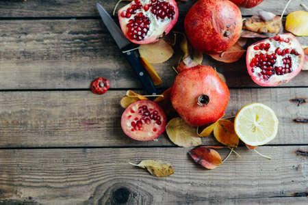 christmas perfume: Ripe pomegranate fruit on wooden vintage background. Red juice pomegranate on dark background.  Fresh juicy pomegranate - whole and cut, top view.  Juicy pomegranates on wood