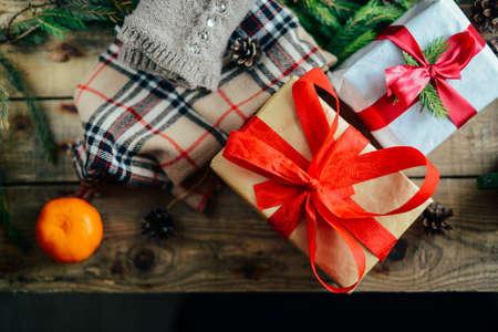 generosa: Extensa serie de disparos de vacaciones con una variedad de accesorios y fondos. Gran cantidad de copyspace para los anuncios. Regalos de Navidad en la mesa de madera. Un par de regalos envueltos en papel de regalo temático de la Navidad.