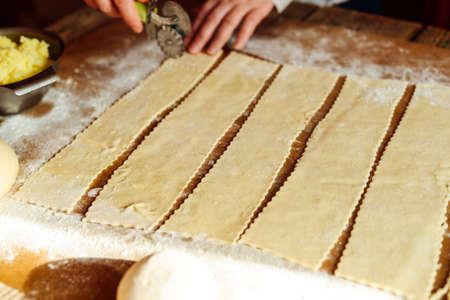 russian food: Making of pierogi with potato Vareniki. Russian food . Rustic style. Vareniki dumplings, pierogi before boiling traditional Ukrainian food. Dumpling recipe.
