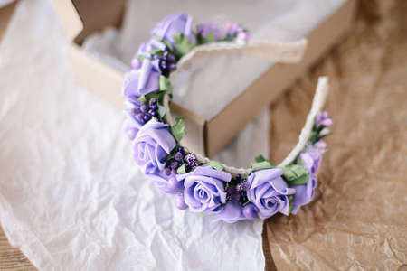 Handmade floral tiara made of  flowers lie on  wooden background. Fashionable hand made wreath of flowers head wear. Hand crafted fashion accessories for women