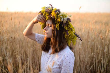 beautiful girl in wreath of flowers in meadow on sunny day. Portrait of Young beautiful woman wearing a wreath of wild flowers. Young pagan Slavic girl conduct ceremony on Midsummer. Earth Day Stock Photo