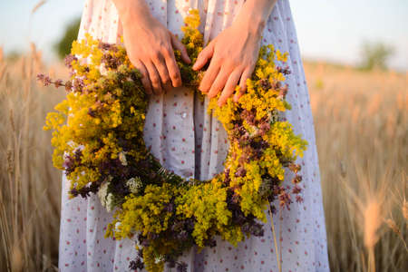 beautiful girl in wreath of flowers in meadow on sunny day. Portrait of Young beautiful woman wearing a wreath of wild flowers. Young pagan Slavic girl conduct ceremony on Midsummer. Earth Day Banque d'images