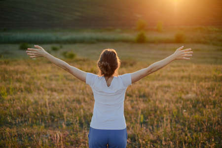 lotus effect: Free woman raising arms to golden sunset. Freedom and success concept. Girl relaxing and enjoying nature. photo of relaxing young woman in nature