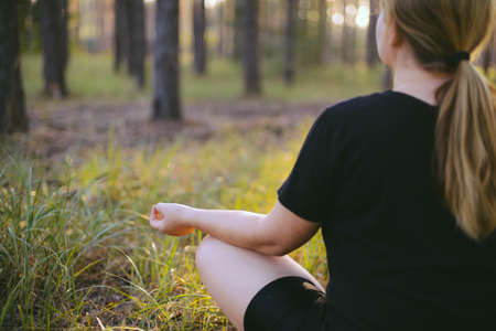 Middle aged woman sitting in lotus position in forest. her eyes are closed. Middle-aged woman in her 40s meditating for exercise outdoors Stock Photo