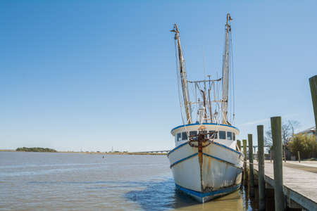 shrimp boat: Old rusty fishing boat tied up to a dock Stock Photo