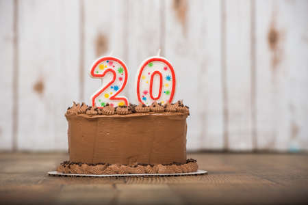Chocolate frosted cake with 20 or twenty candles on it
