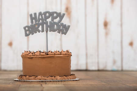 topper: Chocolate frosted cake with silver happy birthday topper